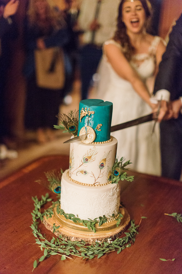 wedding cake beeing cut with a sword