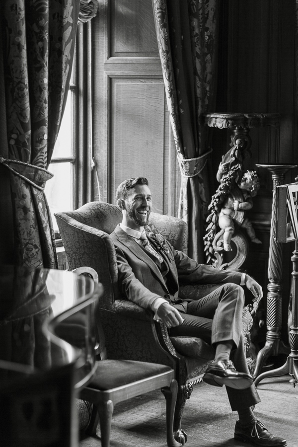 groom laughing sitting on a char at arkinglas estate hall
