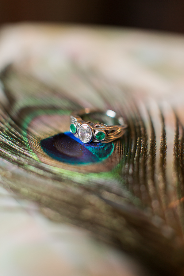 engagement ring with diamond and green stones on peacock feather