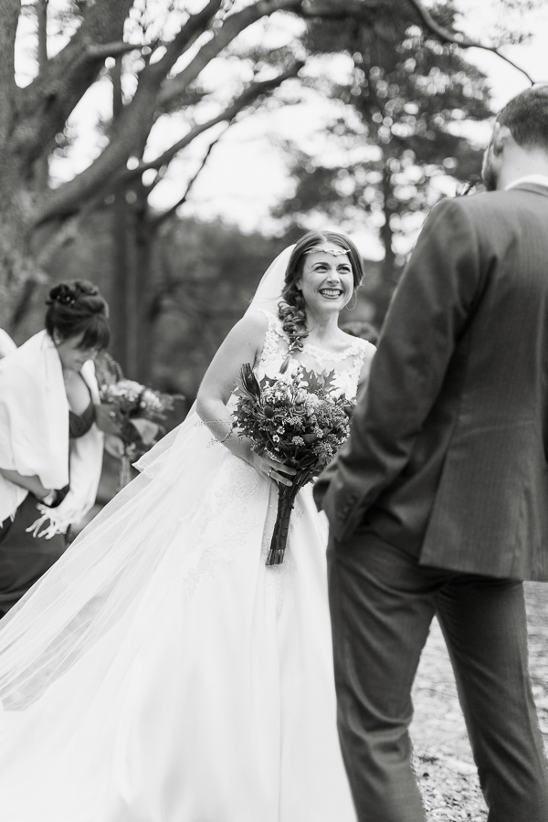 brdie and groom laughing at ceremony outside