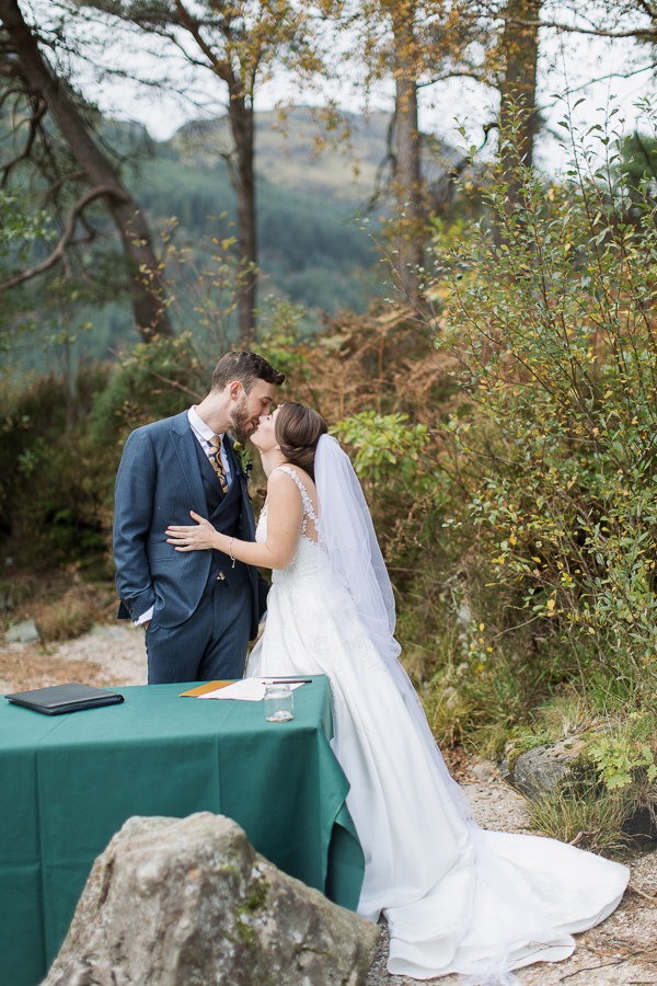 bride and groom kissing before signing paper work during ceremony
