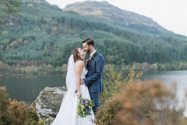 bride and groom embraced on top of a hill at loch eck near glasgow