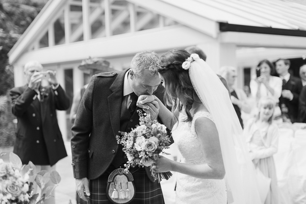 groom kissing bride in her hand before ceremony