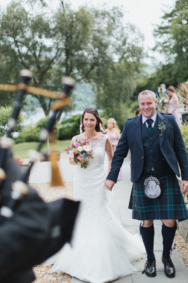 wedding photographer glasgow bride and groom leaded by piper after ceremony