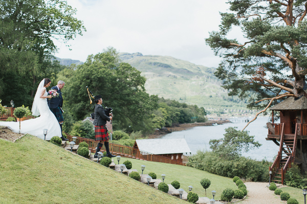 bride and groom walking down stairs with piper at the lodge on loch goil
