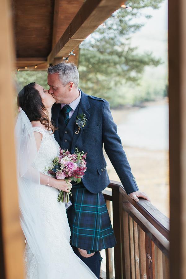 bride and groom kissing on tree house balcony scotland