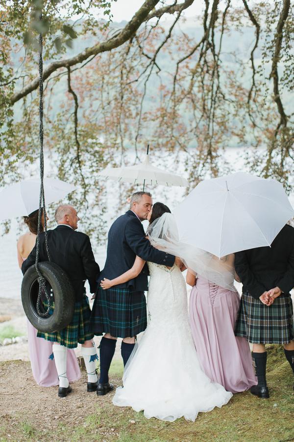 bridal party under big tree with umbrellas