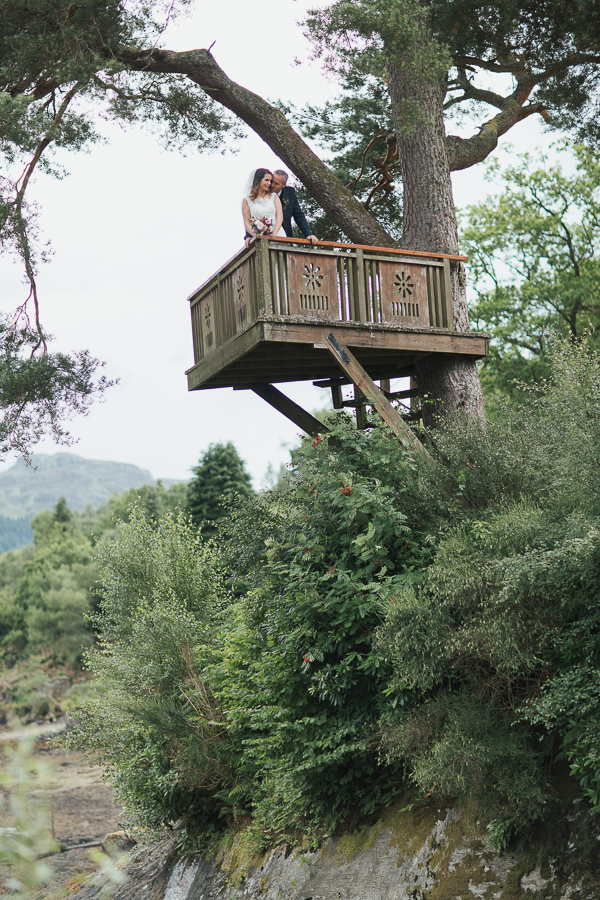 bride and groom embraced on a tree podium