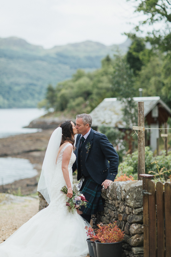 newlyweds kissing in a garden of at the lodge on loch goil