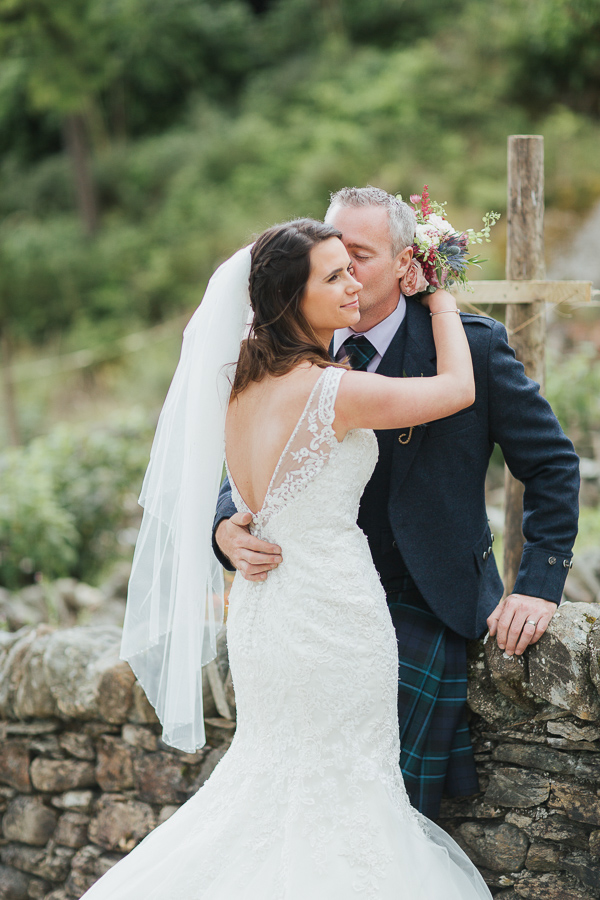 groom kissing bride on a cheek