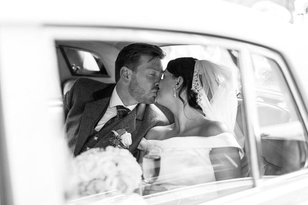 newlyweds kissing in the wedding car in glasgow