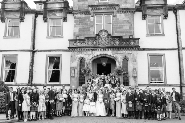 whole wedding party group at steps in front of cameron house