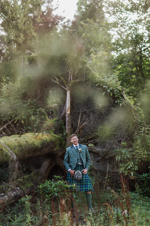 portrait of groom smiling next to a fallen tree at cameron house land