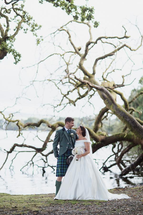 wedding photographer glasgow loch lomond fallen tree with bride and groom