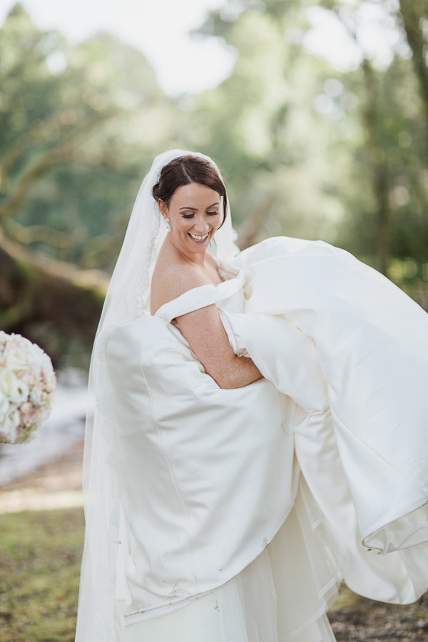 bride laughing lifting her dress at cameron hosue wedding