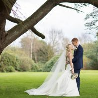 young married coupke standing under large tree mar hall wedding