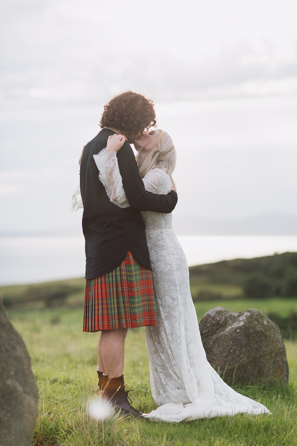 bride and groom kissing on a scottish hill
