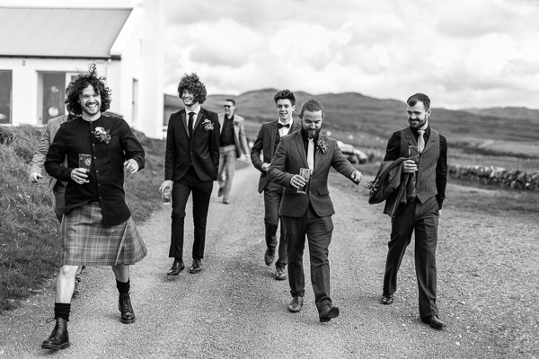 groom and groomsmen laughing and drinking beer