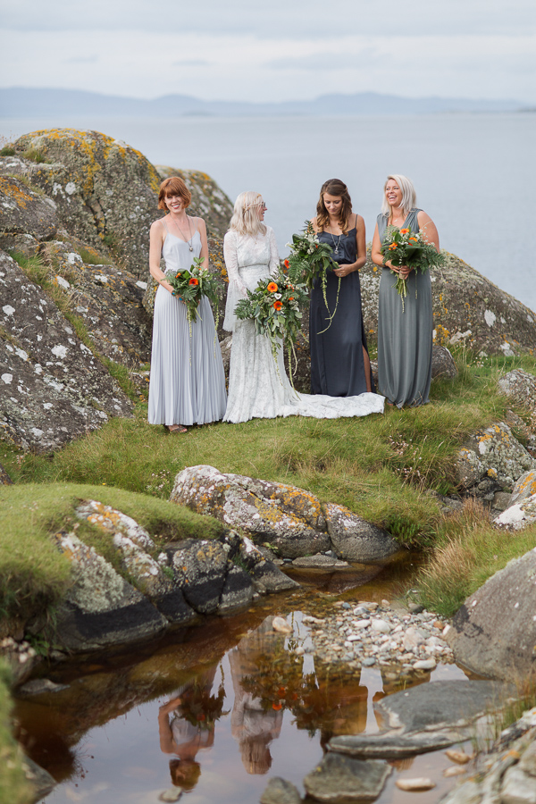 bridesmates standing on a rocky beach in scotland
