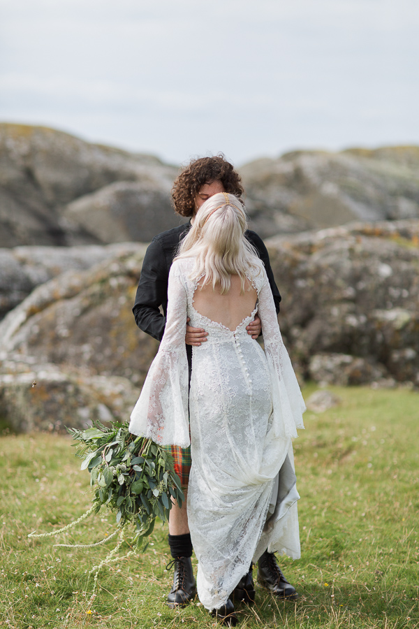 bride and groom kissing on a rocky beach