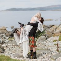 wedding photographer groom lifting bride on a rocky beach at crear scotland wedding