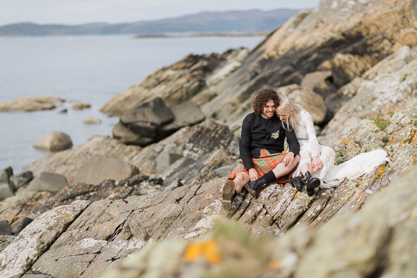 bride and groom sitting on a rocky coast