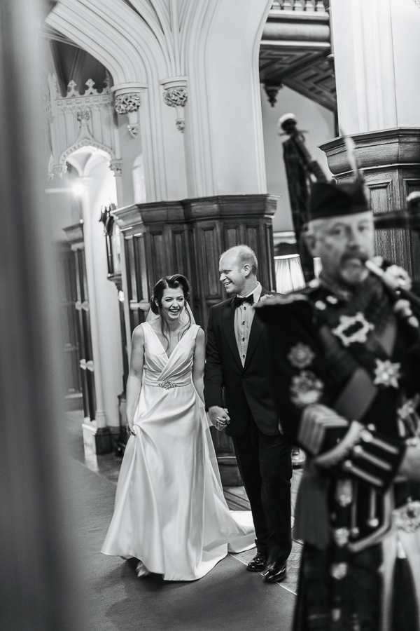 bride and groom laughing beeing leaded by scottish piper