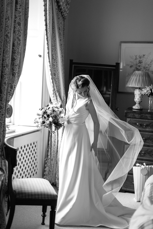 bride fixing her dress just before leaving for ceremony