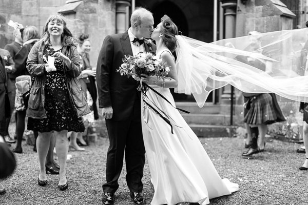 fotogenic of scotland bride and groom kissing outside church in scotland veil is lifted by wind