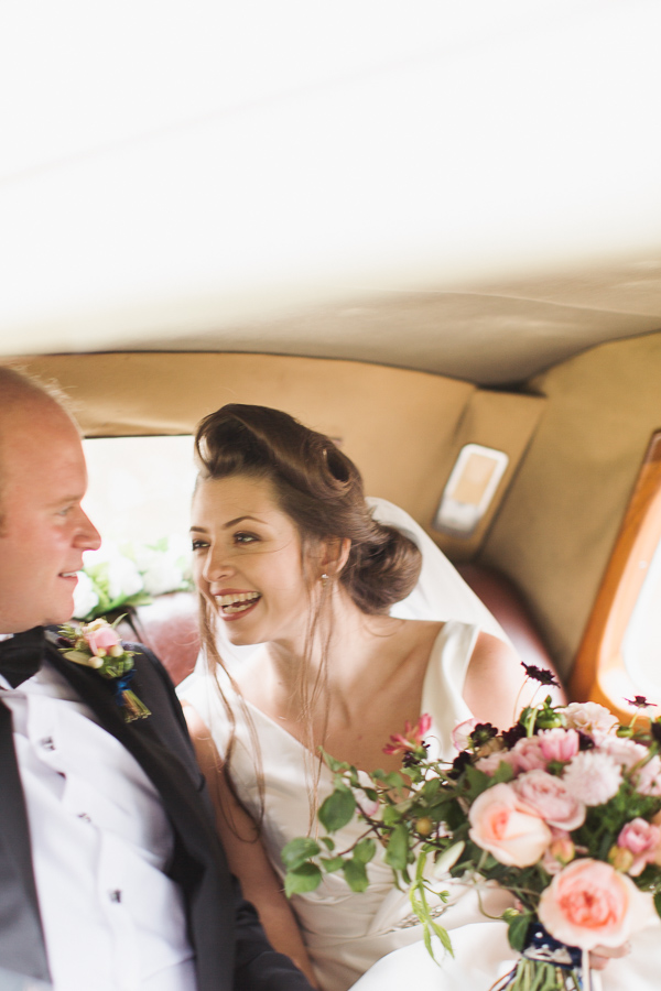 bride smiling at groom inside the wedding car