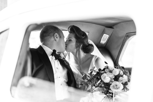 newlyweds kissing inside wedding car