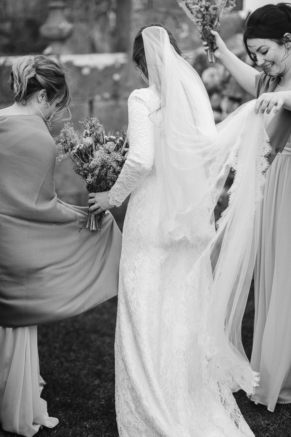 bride and bridemsates fixing dresses
