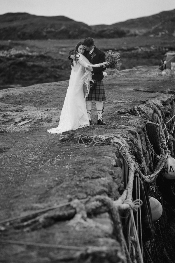 newlyweds embraced standing on an old pier