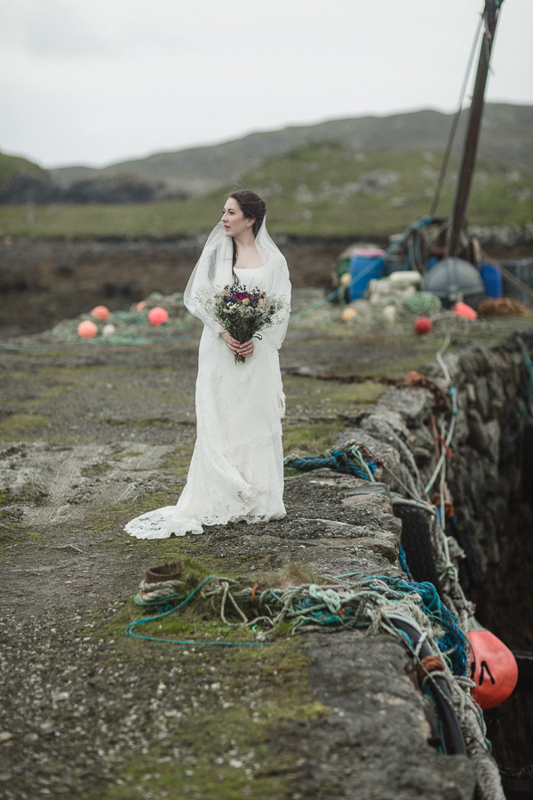 bride standing alone on a scottish pier