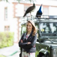 portrait of engaged girl with landrover and peacocks