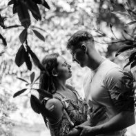 young couple embraced betwen leaves in summer engagement photos