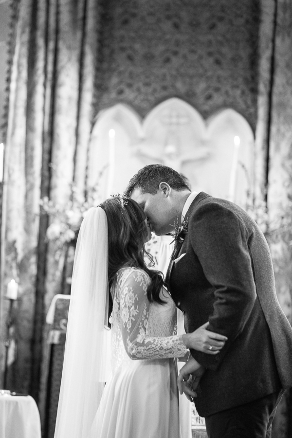 a couple kissing in the chapel at cromlix house