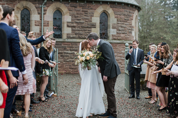 a couple kiss outside of the chapel cromlix