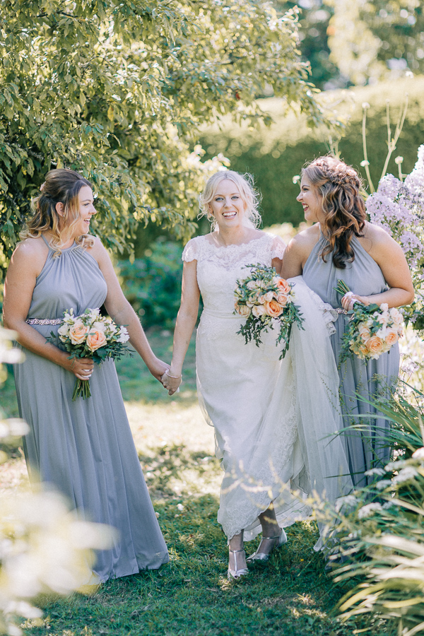 bride smiling and hloding hands with bridesmaids loch lomond