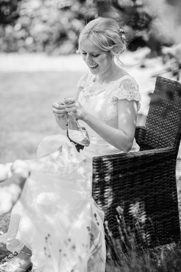 bride in her garden puttign her shoes on