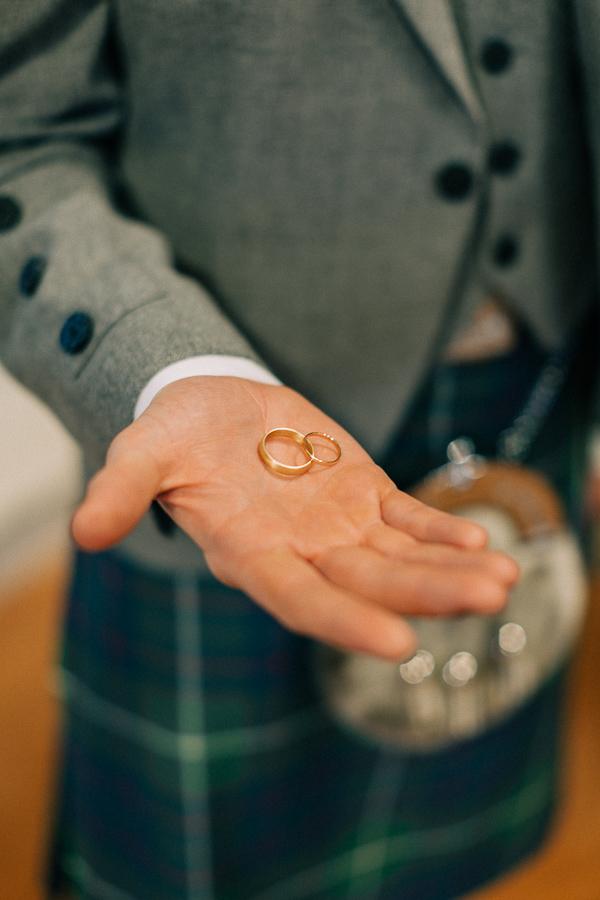 groom holds rings