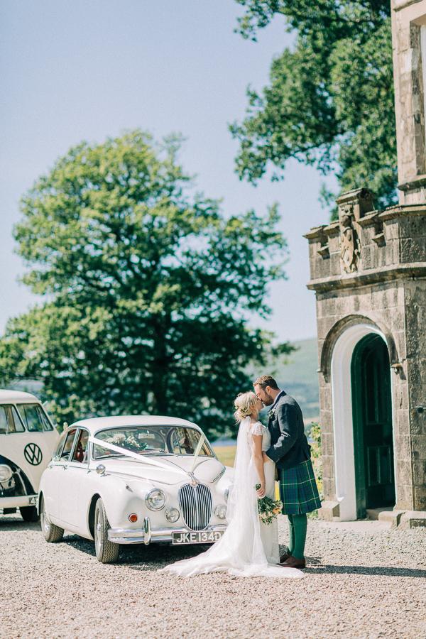 couple kissing outside of a castle loch lomond