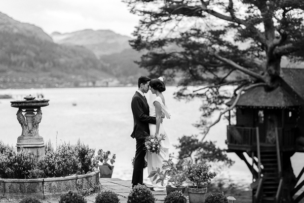 married couple embraced next to vintage fountian with tree house and loch goil in background