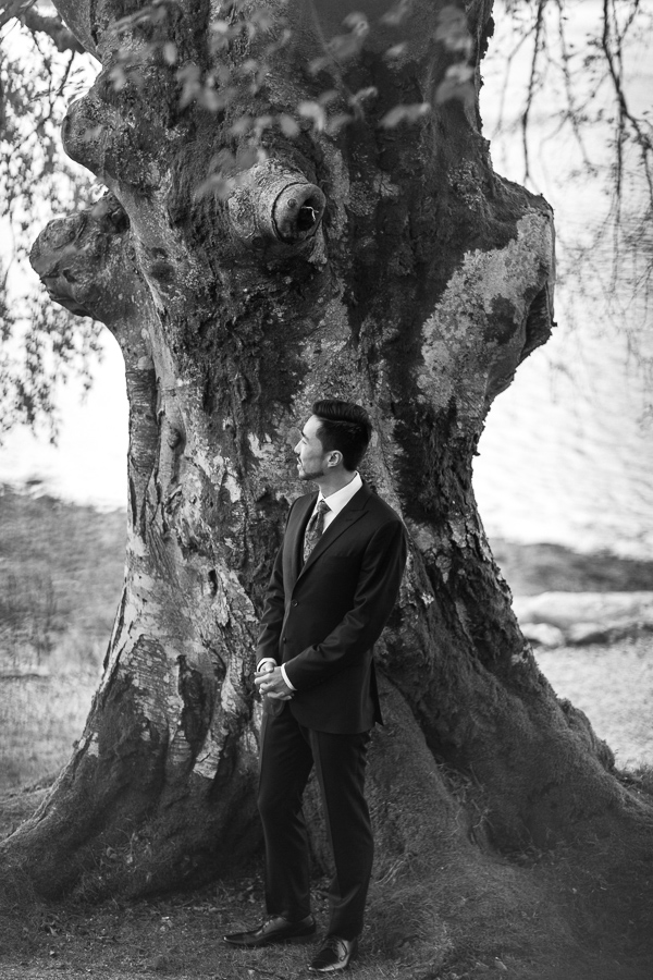 groom next to a large tree