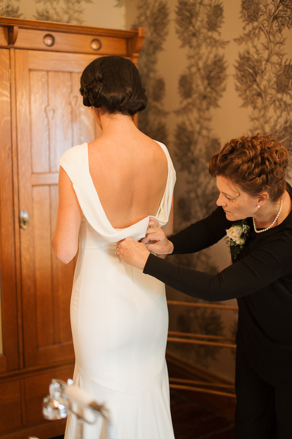 mother of the bride zipping the wedding dress