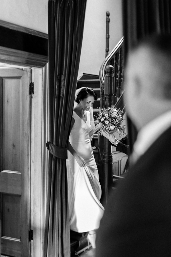 bride walking down stairs while father is looking