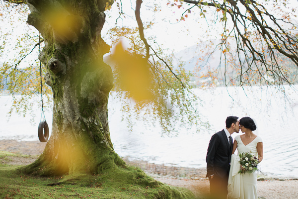 bride and groom kissing with large tree and loch in the background