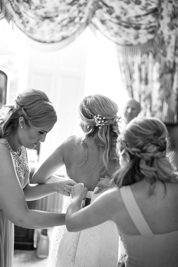 bridesmates helping bride to get into wedding dress