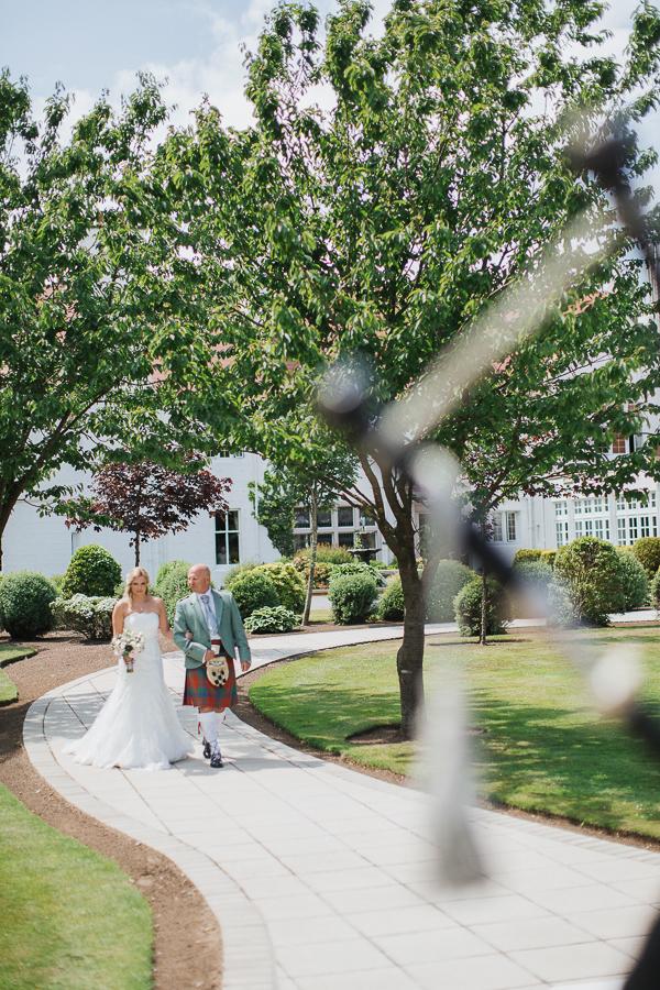 bride walking down in teh garden for ceremony at lochgreen hotel
