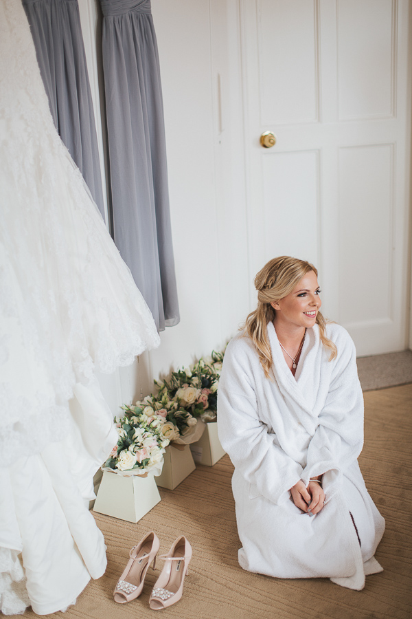 bride sitting next to her dress and flowers at lochgreen wedding preparations
